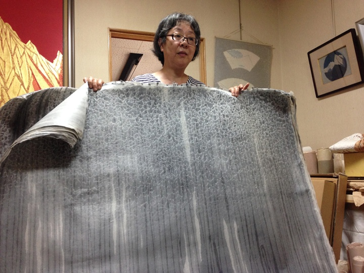 Mrs. Kano holding up sheets of Washi paper that are hand made at the family studio.